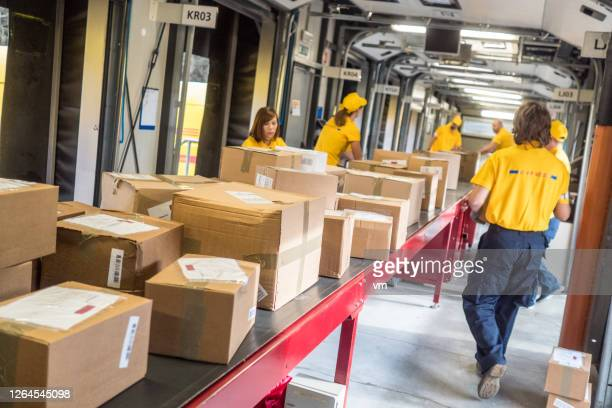 postal workers handling packages at a conveyor belt - post structure stock pictures, royalty-free photos & images
