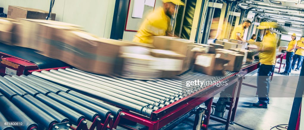Postal workers inspecting packages on a conveyor belt : Stock Photo