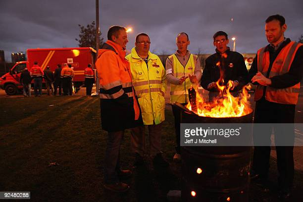 Postal workers warm themselves beside a brazier on the picket line at Glasgow mail centre on October 29 2009 in Glasgow Scotland Mail centre staff...