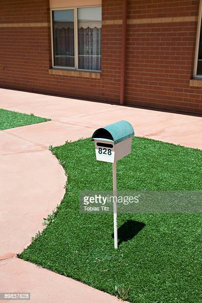 A postbox on a lawn outside of a house