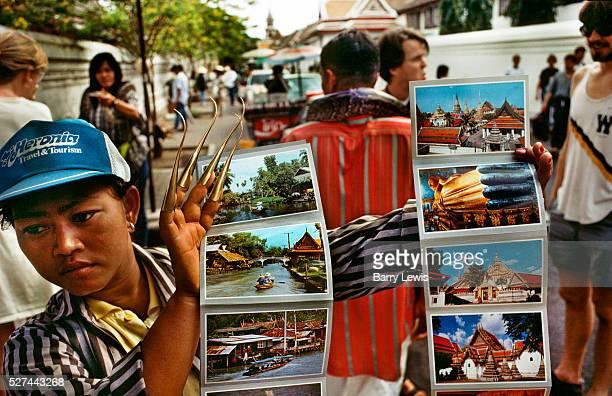 Postcard and souvenir seller wearing golden 'Thai Fingers' outside the Grand Palace Bangkok