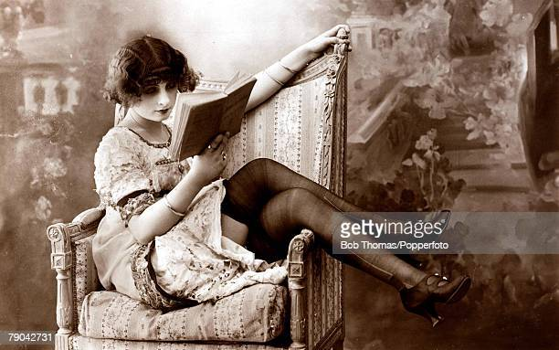 Postcard circa 1920 Young dark haired woman reading a book with her legs draped over a chair