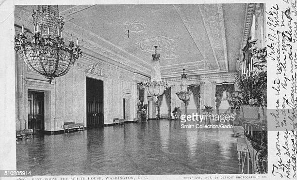 Postcard created from a photograph, shows the East Room of the White House decorated with ornate chandeliers, the room is lined with small pieces of...