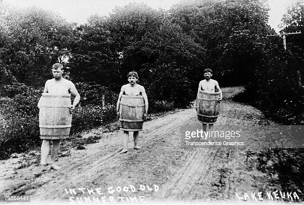 Postcard entitiled 'In the Good Old Summertime' shows three men apparently naked but for wooden barels as they walk along a dirt road near Lake Keuka...