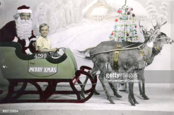 Postcard features a colorized photo of a Santa Claus in a sled with a young boy the latter of whom holds the reins of a pair of reindeer circa 1910