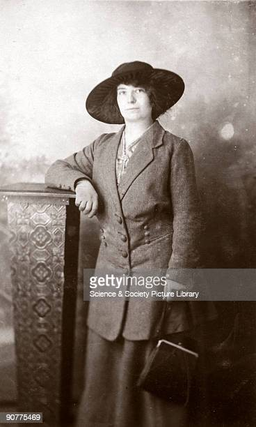 Postcard featuring a studio portrait of a smartlydressed young woman wearing a hat and holding a handbag On the reverse the woman has written 'To...