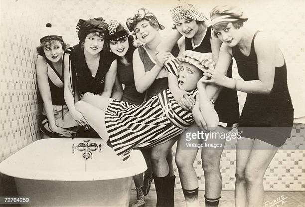 Postcard image by Evans shows the young slapstick comedy actresses known as the 'Mack Sennett Bathing Beauties' as they gather around a bathtub to...