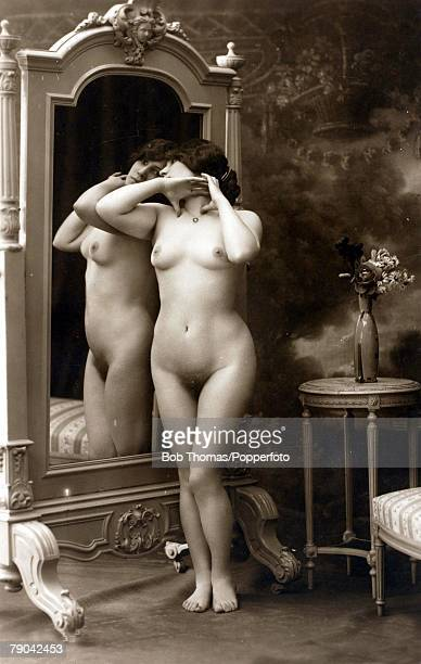 Postcard Nude circa 1910 Naked dark haired woman standing in front of an ornate mirror full frontal