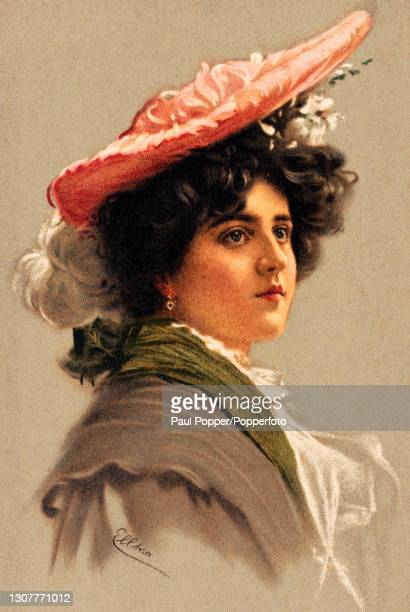 Postcard of a young woman from the Girls of Today series, she wears a brown cape with an olive green scarf and a large, flat peach coloured silk hat...