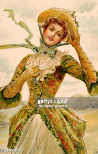 Postcard of a young woman wearing a green and red fitted coat over a pale coloured dress, she wears elbow length gloves and a straw bonnet tied under...