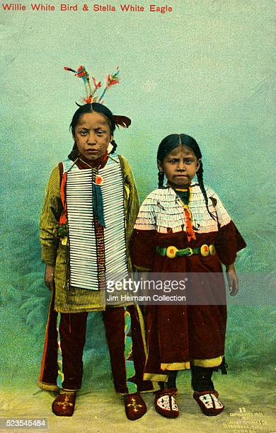 Postcard of two North American Indian children Willie White Bird and Stella White Eagle dressed in traditional clothing including feathers and...