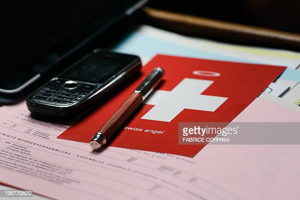 A postcard showing a Swiss flag with a halo on the top is seen at the desk of member of Parliament Manuel Tornare during the election meeting of the...