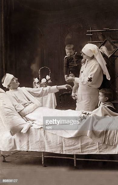 Postcard 'We wish you good health and best wishes of good years' A nurse bring the children of a wounded 1914
