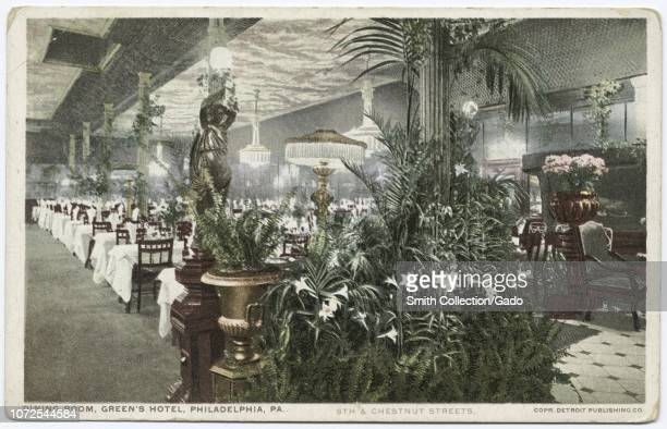 Postcard with a color image of the Green's Hotel dining room or restaurant seating area with ferns palms and lilies decorating a columnar support in...
