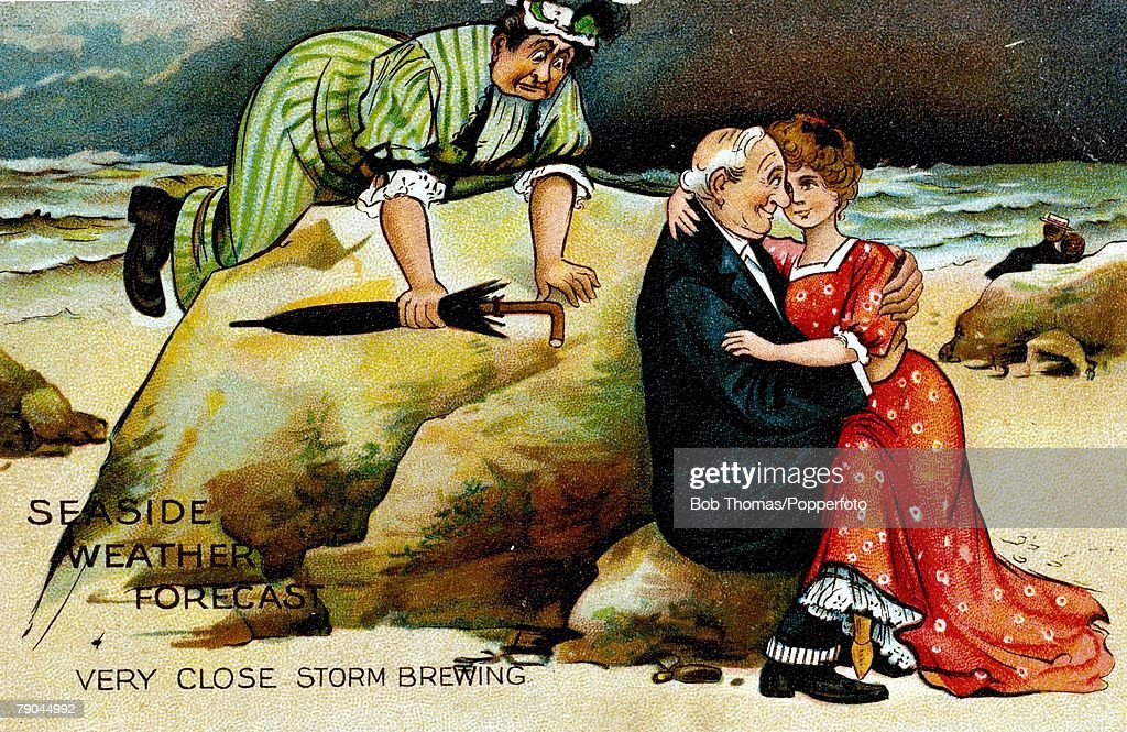 Postcards. Circa 1910. A colour illustration of a mature man sitting holding a younger woman on his lap whilst sitting on some rocks on a beach, also pictured is his mature wife kneeing on top of a large rock after having caught him being unfaithful. : News Photo