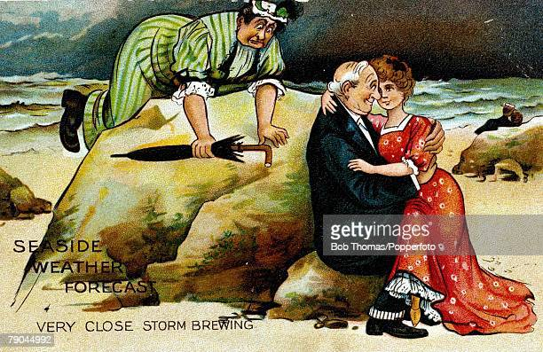 Postcards Circa 1910 A colour illustration of a mature man sitting holding a younger woman on his lap whilst sitting on some rocks on a beach also...