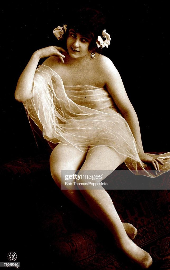 Postcards. Circa 1915. Dishabille. A picture of a woman sitting down with a light coloured gossamer wrap over her, posing for the camera. : News Photo