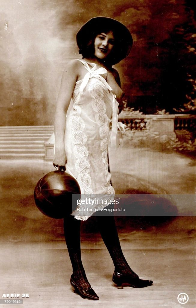 Postcards. Circa 1915. Dishabille. A picture of a woman wearing a nightdress, partially revealing a breast whilst holding a ball posing for the camera. : News Photo