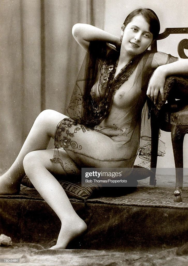 Postcards. Circa 1915. Dishabille. A picture of a woman wearing a black see through wrap which reveals her breasts whilst sitting posing for the camera. : News Photo