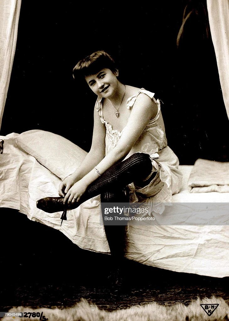 Postcards. Circa 1915. Dishabille. A picture of a woman wearing an undergarment and corset whilst sitting on a bed posing for the camera. : News Photo