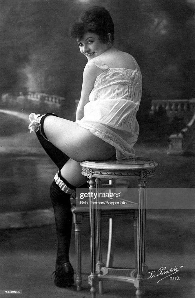 Postcards. Circa 1915. Dishabille. A picture of a woman wearing an undergarment whilst sitting on a small table posing for the camera. : News Photo