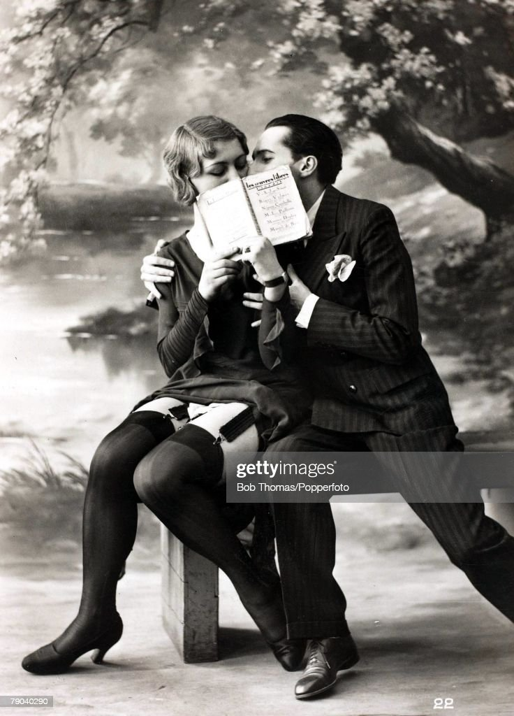 Postcards. Circa 1920. A picture of a romantic couple kissing behind an open book whilst sitting together on a bench. : News Photo