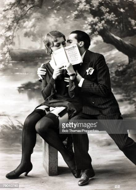 Postcards Circa 1920 A picture of a romantic couple kissing behind an open book whilst sitting together on a bench