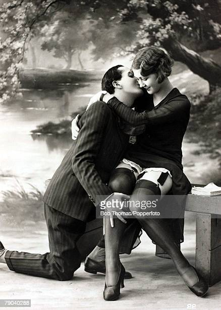 Postcards Circa 1920 A picture of a romantic couple kissing whilst sitting together on a bench
