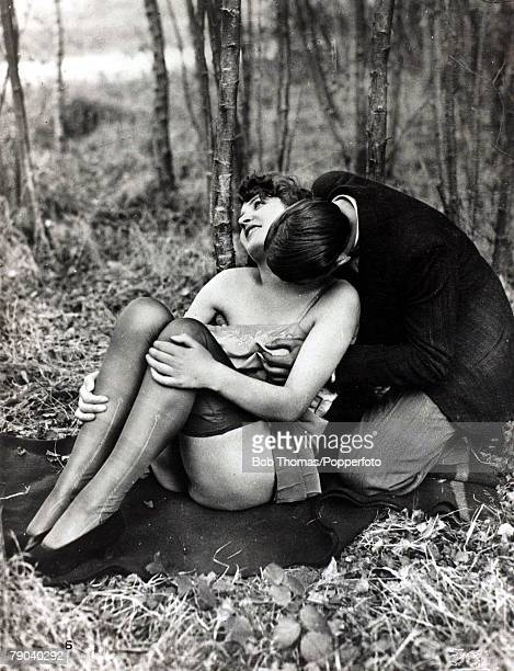Postcards Circa 1920 A picture of a romantic couple sitting together in the woods kissing and making love
