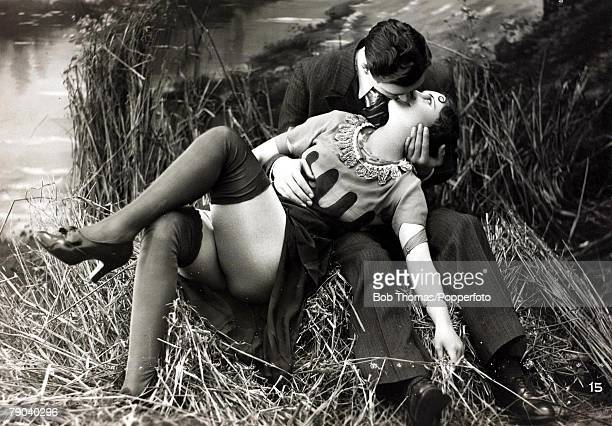 Postcards Circa 1920 A picture of a romantic couple sitting together kissing in some long grass by a lake