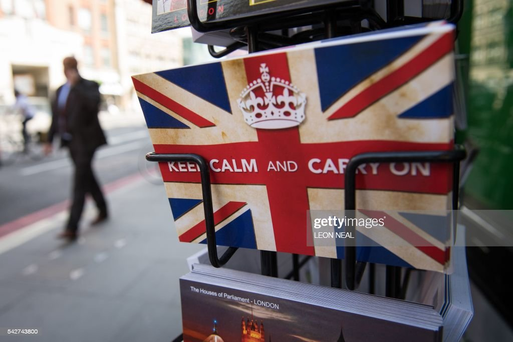 TOPSHOT - Postcards featuring the World War II British slogan 'Keep Calm and Carry On' are seen outside a newsagents in London, on 24 June, 2016. Britain voted to break away from the European Union on June 24, toppling Prime Minister David Cameron and dealing a thunderous blow to the 60-year-old bloc that sent world markets plunging. /