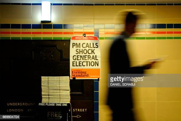 A poster above a newspaper stand advertises today's Evening Standard with the front page story relating to British Prime Minister Theresa May's call...