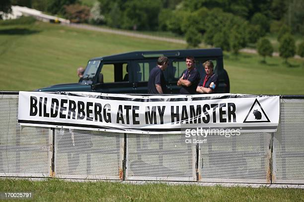 Poster adorns the security barrier of the protester encampment outside The Grove hotel, which is hosting the annual Bilderberg conference, on June 6,...