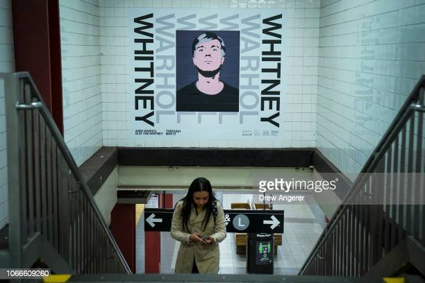 A poster advertisement for The Whitney Museum's new Andy Warhol retrospective hangs on the wall as a commuter walks through the 14th Street/Eighth...