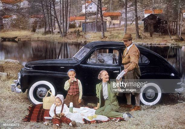 Poster advertising a Volvo 444 1953 A family picnicing in front of their car by the side of a lake