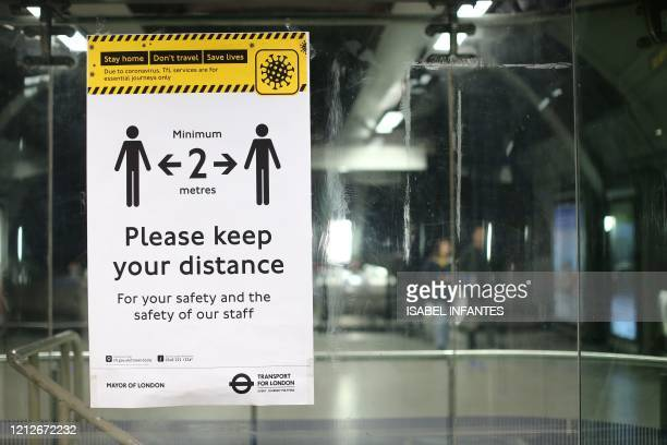 A poster advising people on social distancing on the London Underground is seen during the evening rush hour at Waterloo station on May 11 as life in...