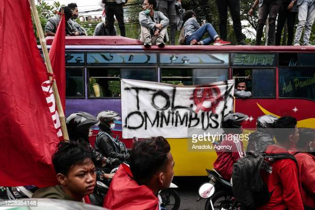 """Poster """"against omnibus law"""" on the bus during a protest against government's labour reform bill omnibus law in Jakarta, Indonesia on October 8,..."""