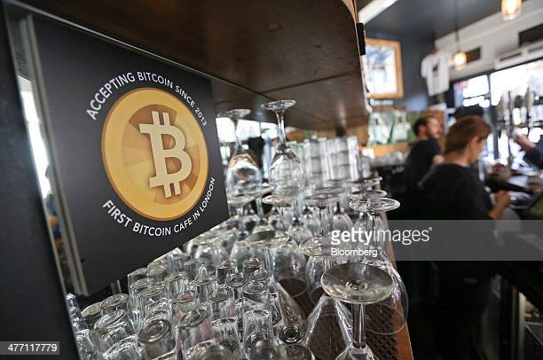 A poster alerting customers that the digital currency Bitcoin is accepted as payment sits behind the counter inside the Old Shoreditch Station cafe...