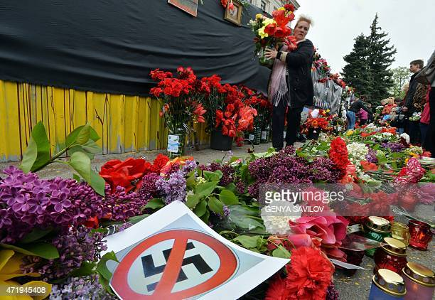 A poster bearing a crossedout swastika lies on flowers as people attend a proRussian meeting at Kulikove Pole Square in Odessa southern Ukraine on...