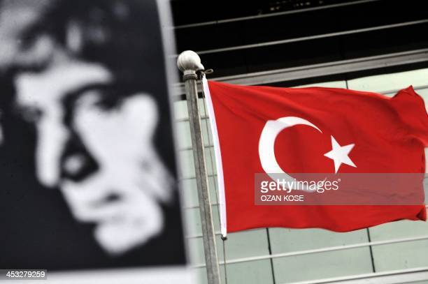 A poster bearing a picture of Hrant Dink and a Turkish flag are pictured in front of the Caglayan Law Court during the retrial of the man accused of...