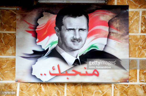 CONTENT] Poster bearing an image of Syria's President Bashar Assad hangs on a Damascus building with We love you written underneath in Arabic