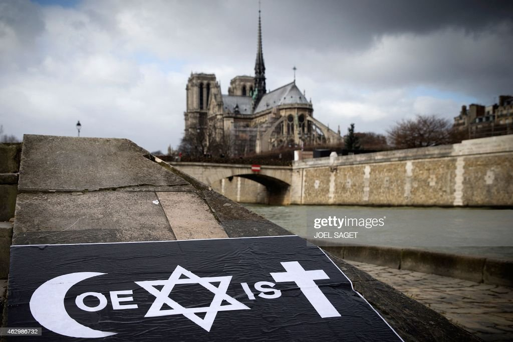 A poster by French street artist Combo is pictured after being stuck on the Quai de la Tournelle, near the Arab World Institute (IMA) on February 8, 2015 in Paris, displaying Combo's message on the coexistence of religions, using intertwined symbols of the Muslim, Jewish and Catholic religions to write the word 'Coexist'. Combo stuck and distributed posters in front of the Arab World Institute (IMA) in Paris on February 8, supported by the institution, after claiming to have been attacked because of his message on the coexistence of religions. Combo said he was attacked on January 31 at Paris' Porte Doree district by four men while he was putting on a wall a poster of himself photographed in a djellaba and associated with the word 'Coexist', using intertwined symbols of the Muslim, Jewish and Catholic religions. The Notre-Dame cathedral is seen behind.