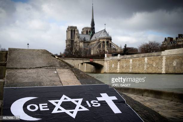 A poster by French street artist Combo is pictured after being stuck on the Quai de la Tournelle near the Arab World Institute on February 8 2015 in...