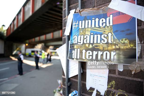 A poster declaring united against terror is stuck on a wall by the police cordon close to the scene of a van attack in Finsbury Park north London on...
