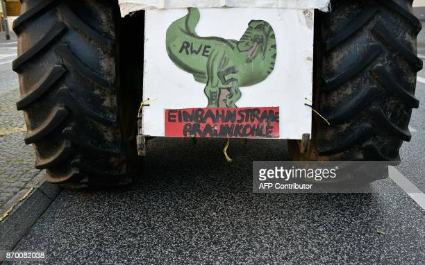 A poster depicting a dinosaur with the logo of German energy supplier RWE and the text OneWay Street Lignite is fixed on a tractor of climate...