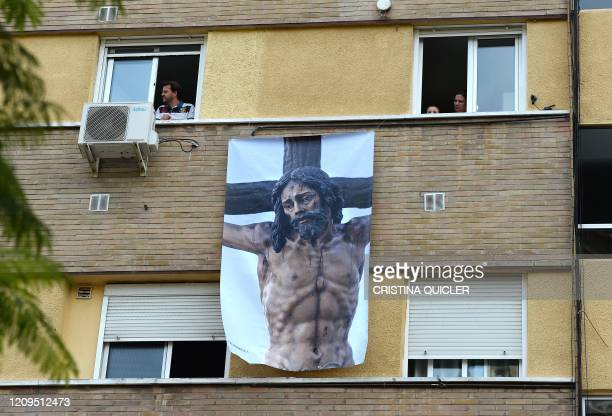 A poster depicting a religious image of Jesus Christ hangs on a facade on April 8 in Seville where Easter processions were cancelled during a...