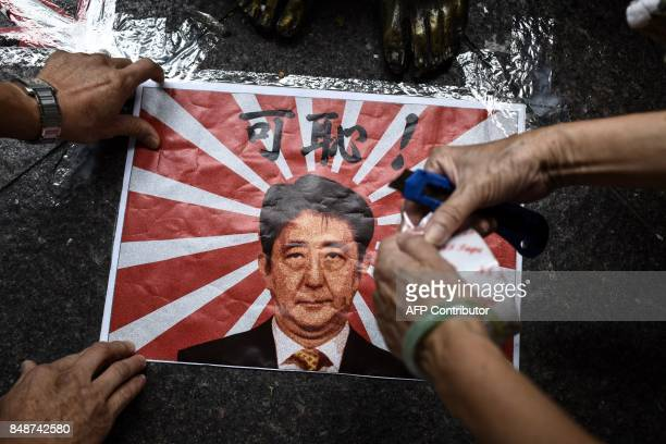 TOPSHOT A poster depicting Japan's Prime Minister Shinzo Abe and the Japanese wartime imperial flag is taped next to the feet of a comfort woman...