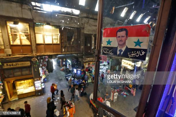 """Poster depicting Syria's President Bashar al-Assad superimposed upon the national flag with text in Arabic reading """"Syria's workers are with you"""" is..."""