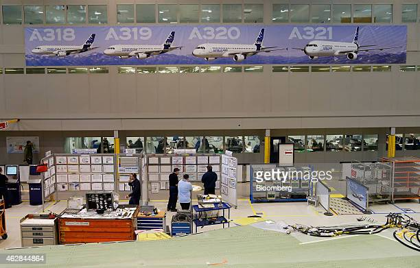 A poster depicting the Airbus A318 A319 A320 and A321 aircraft hangs on a wall above workers inside the A320/A330 wing assembly building at Airbus...