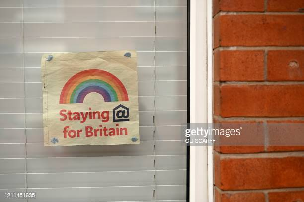 Poster depicting the colours of a rainbow, being used as symbols of hope during the COVID-19 pandemic, is pictured in the window of a house in...